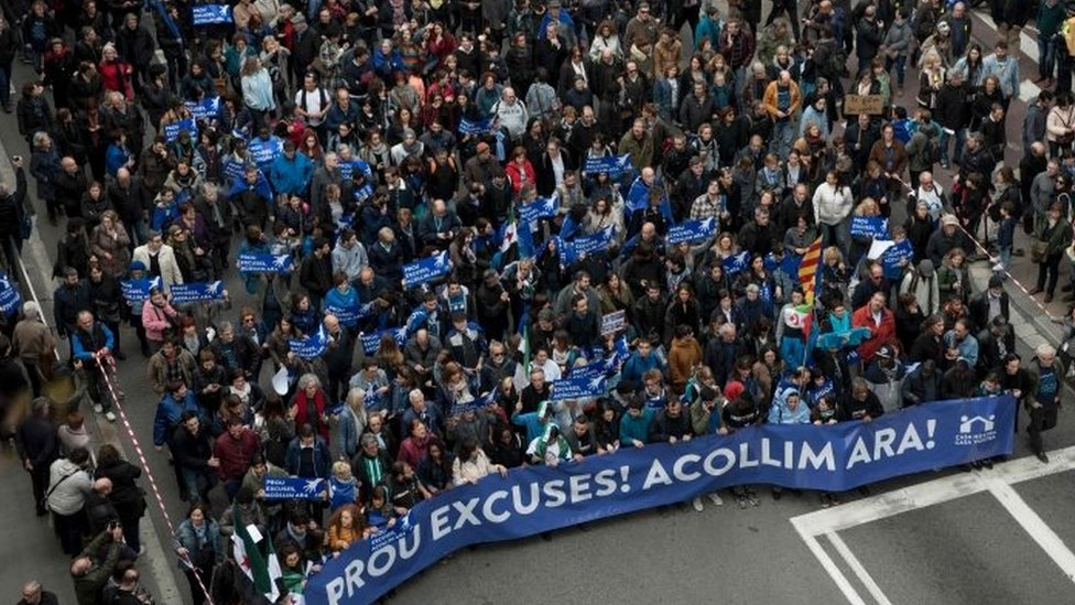 """Some of thousands of people hold a banner reading """"Enough excuses! Let's welcome now"""" as they walk in a street of Barcelona (18 February 2017)"""