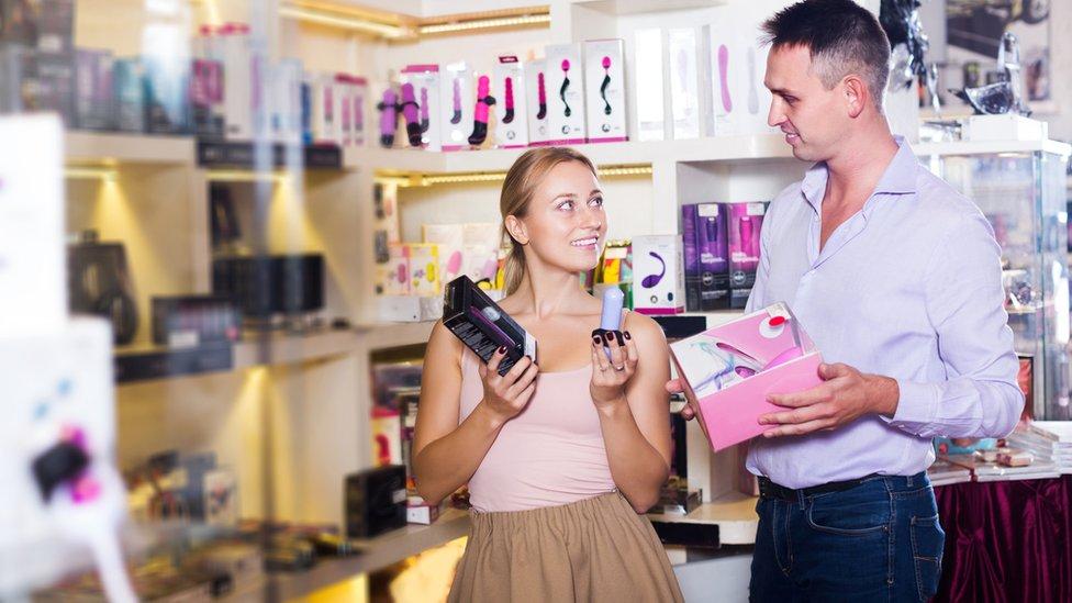 Una mujer y un hombre en un almacén de juguetería sexual