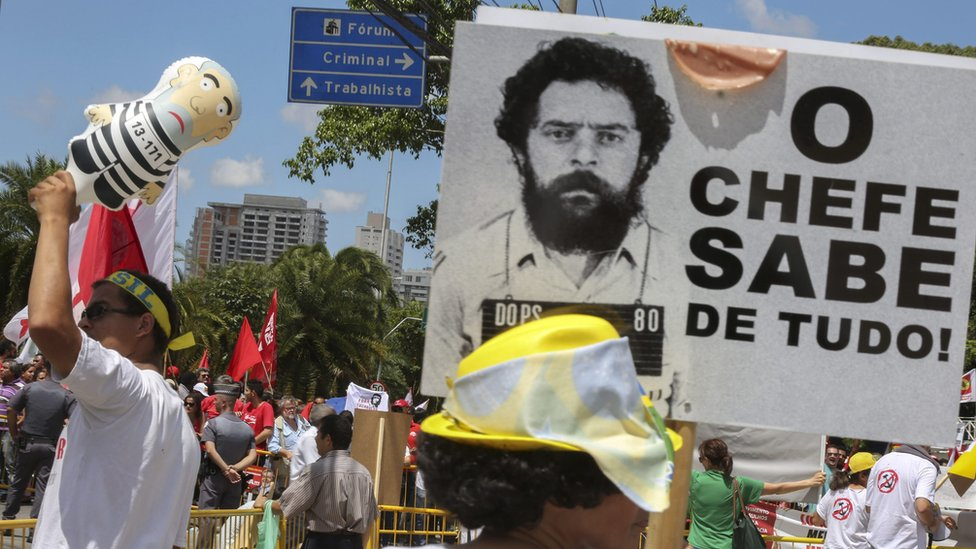 """Demonstrators for and against Lula. The banner reads: """"The boss knows about everything"""""""