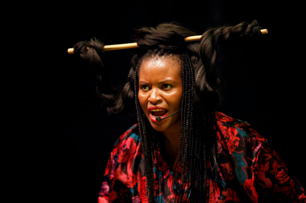 A woman sings into a microphone with her hair wrapped around a baton in an ornate style