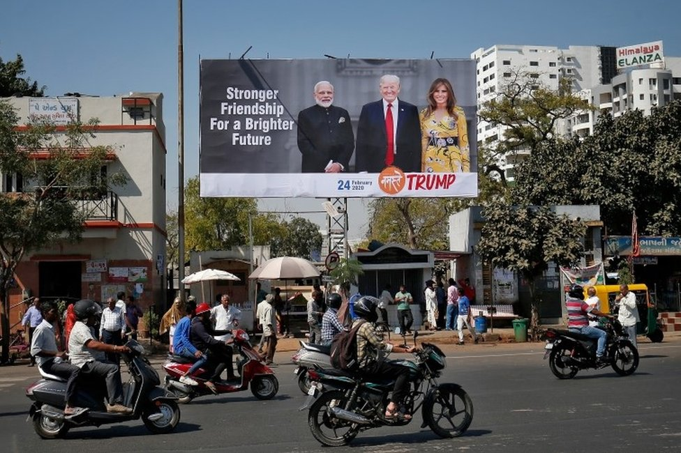 """People ride their motorbikes past a hoarding with the images of India""""s Prime Minister Narendra Modi, U.S. President Donald Trump and first lady Melania Trump ahead of Trump""""s visit, in Ahmedabad, India, February 18, 2020."""