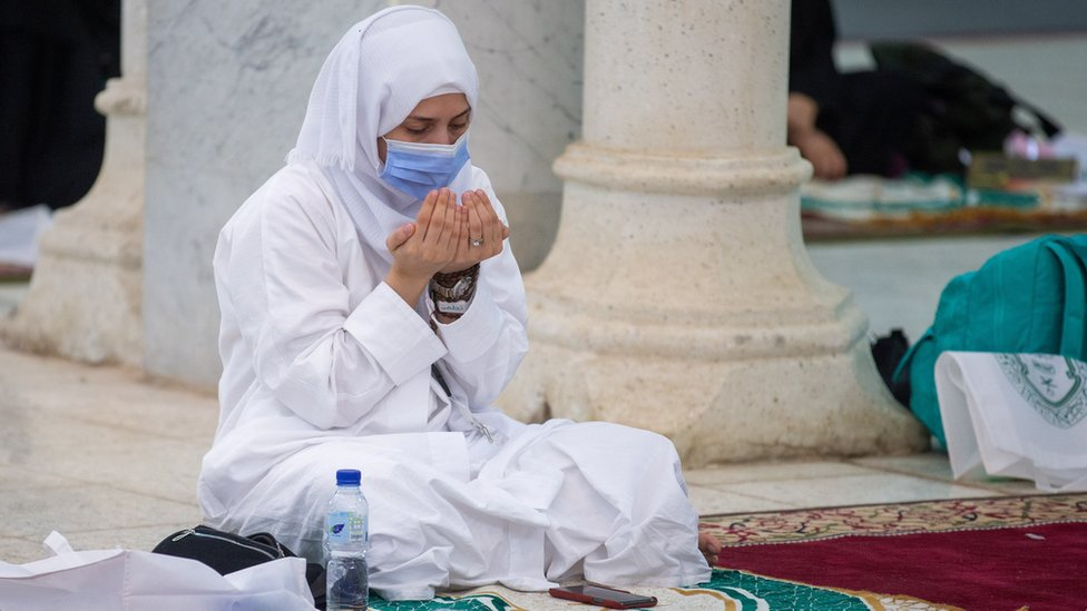 "A Muslim pilgrim wears a mask as she prays inside the Namira Mosque in Arafat to mark the Hajj""s most important day, Day of Arafat (30 July 2020)"