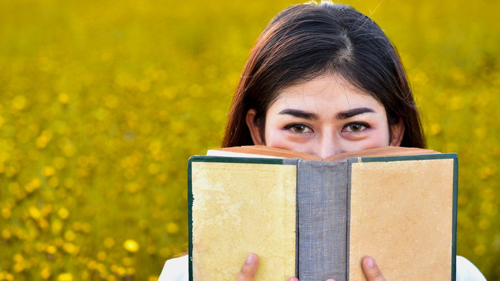 Una joven huele un libro.