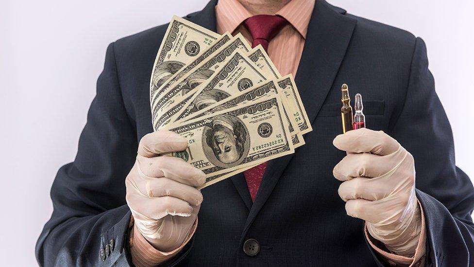 Um homem usando luvas de látex, segurando vacinas em uma mão e dinheiro na outra