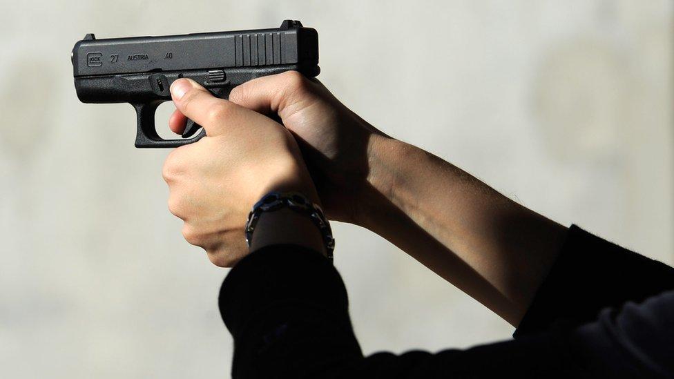 A woman's hands rest on the trigger of a Glock 27 .40 caliber handgun