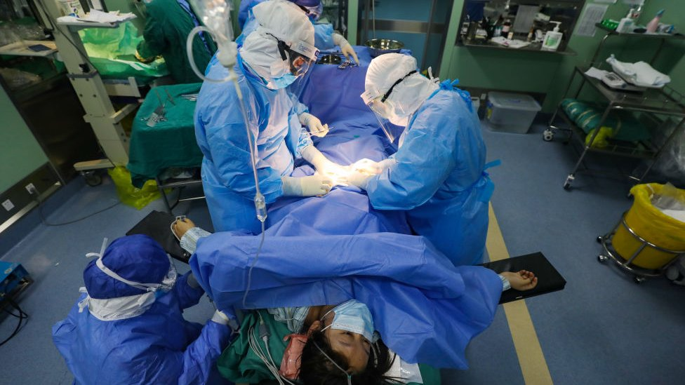 Medical workers perform the Cesarean section operation on a suspected COVID-19 patient in Wuhan Union Hospital in Wuhan in central China`s Hubei province Saturday, March 07, 2020.