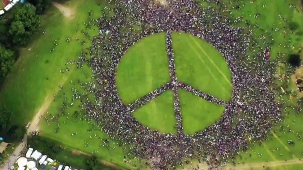 El símbolo de la paz hecho por y con personas en Glastonbury.