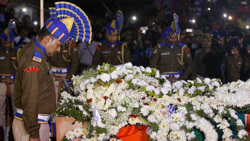 Central Reserve Police Force (CRPF) officers bow to pay tribute next to a coffin containing the remains of their colleague Bablu Santra in Howrah, West Bengal