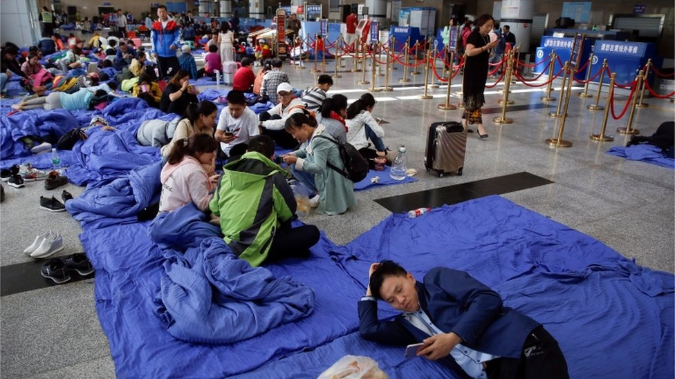Stranded passengers rest at the departure hall of Jiuzhaigou airport near the remote, mountainous area struck by a deadly earthquake in Sichuan province