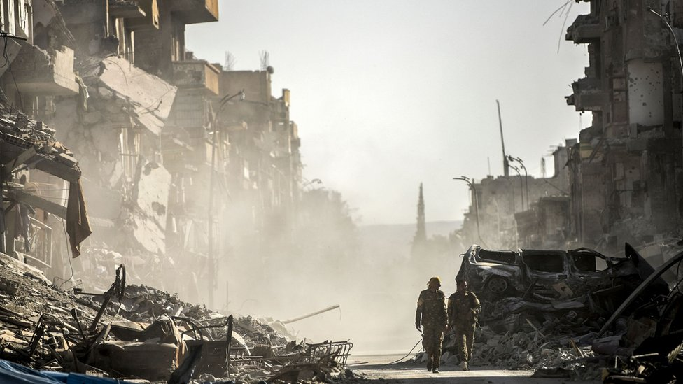 Syrian Democratic Forces (SDF) fighters walk down a devastated street in Raqqa, Syria (20 October 2017)