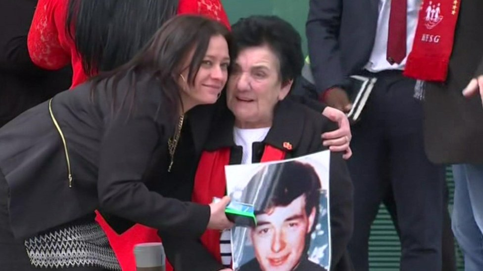 Relatives hugging and holding large photo of a relative who was killed at Hillsborough