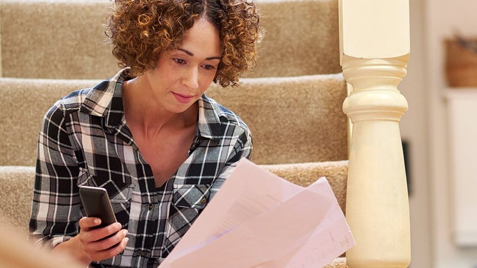 A woman sitting on the stairs holding a phone and some bills