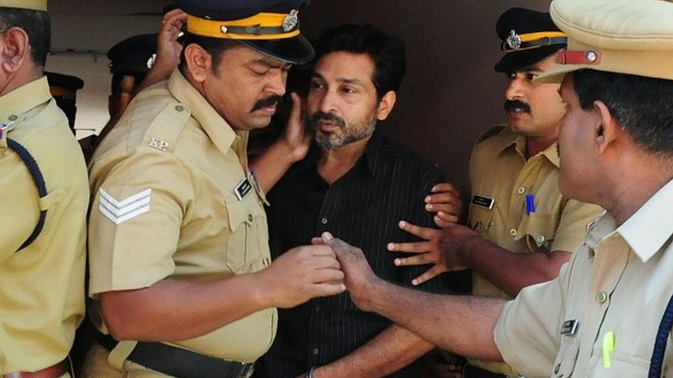 Indian police personnel escort murder suspect Muhammad Nisham (C), accused of fatally wounding a security guard by driving into him with his car, at the Judicial Magistrate's Court in Thrissur on March 11, 2015.