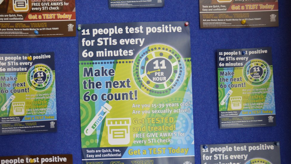 "Posters on health clinic wall read: ""11 people test positive for STIs every 60 minutes - Make the next 60 count!"""