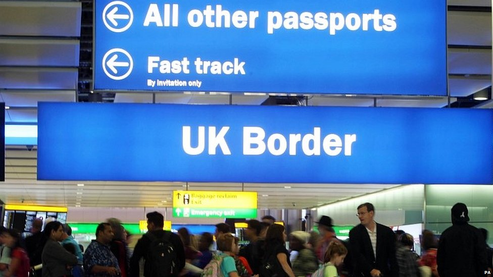 Travellers queuing as passport control at Heathrow airport