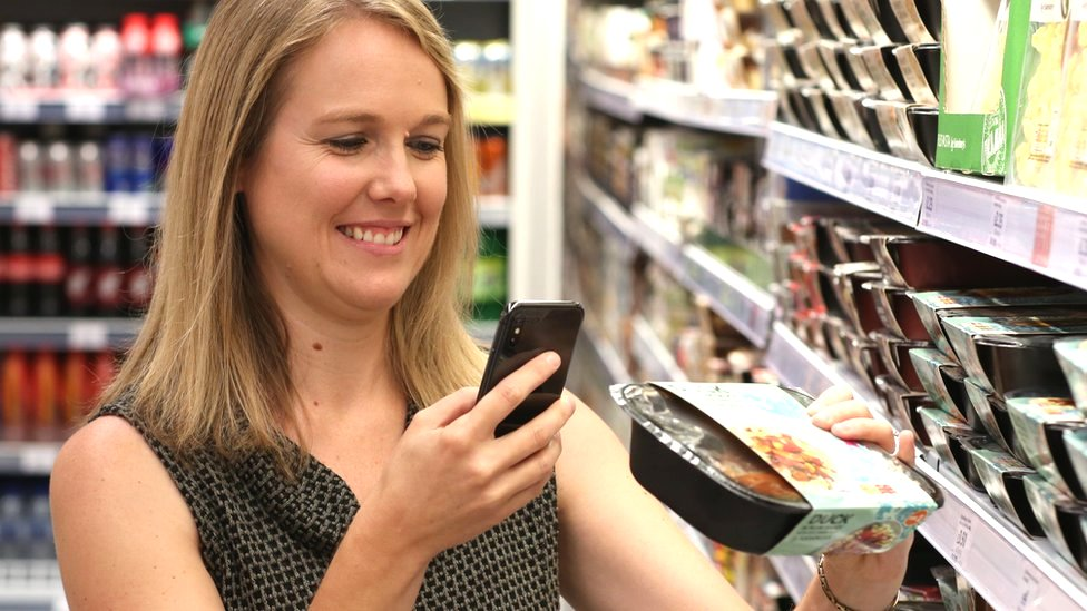 A shopper scanning a product with a smartphone