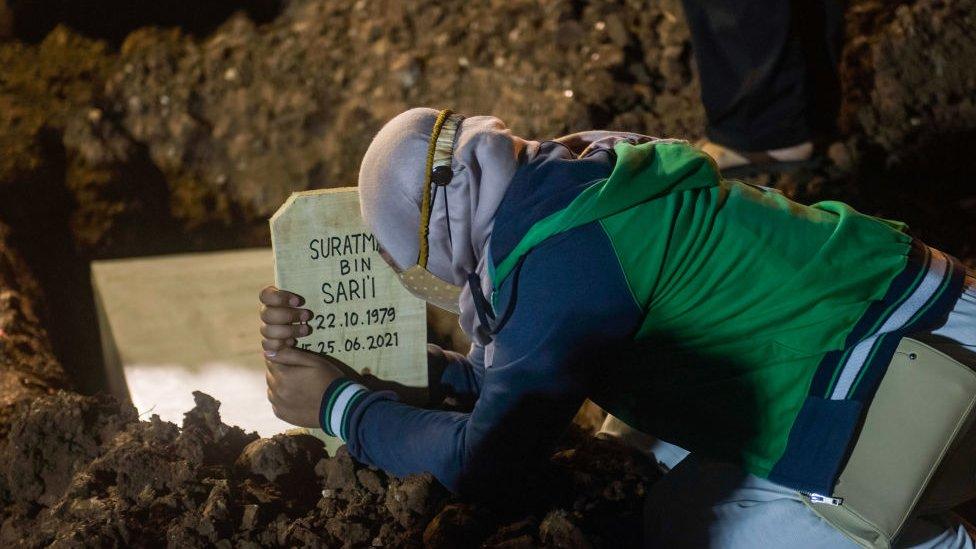 Persona llorando en una tumba en Indonesia en plena ola de coronavirus.