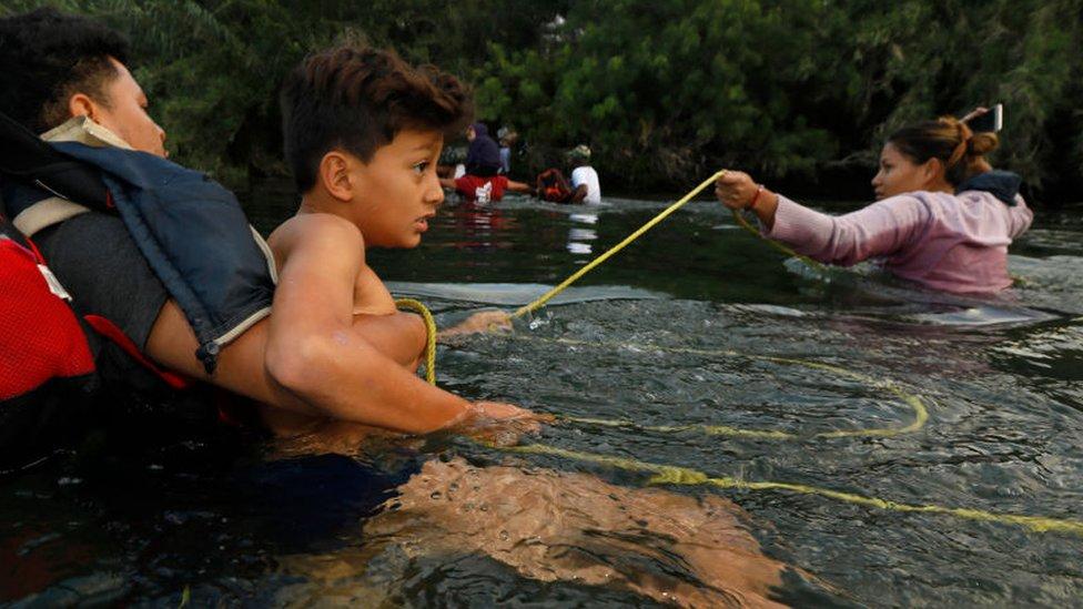 Una familia se sujeta a una soga para cruzar el río