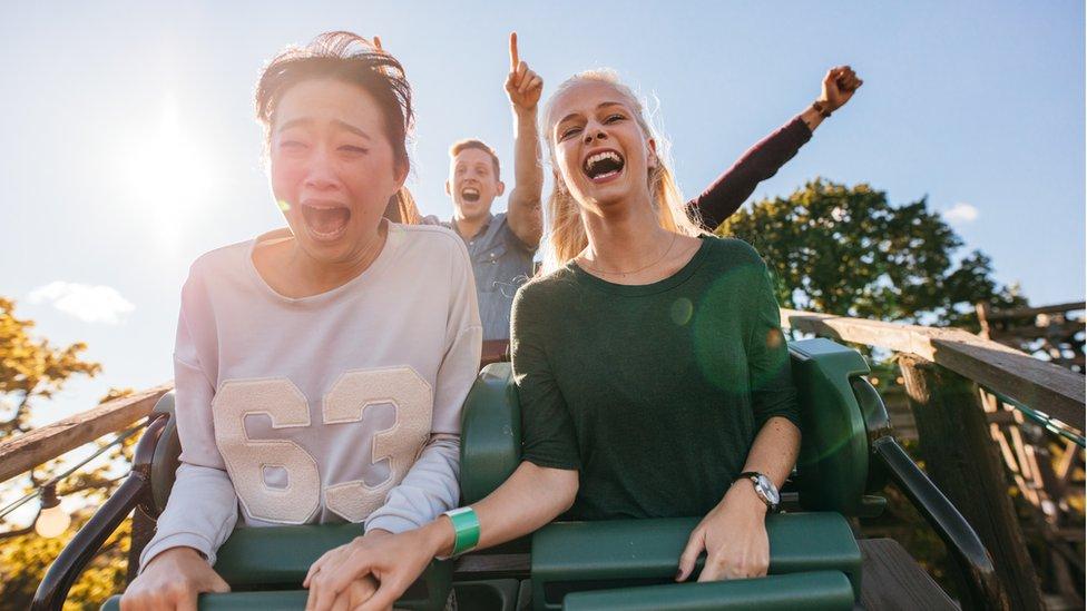 Dos mujeres gritan en una montaña rusa, con amigos en segundo plano