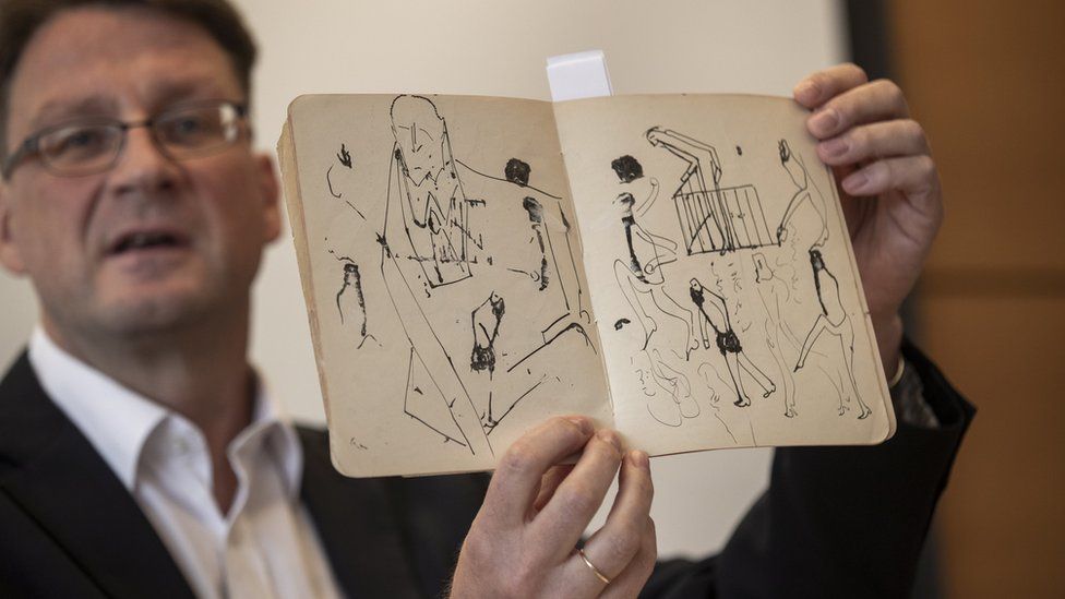 Stefan Litt, from the National Library of Israel, holding up a book of Kafka's drawings