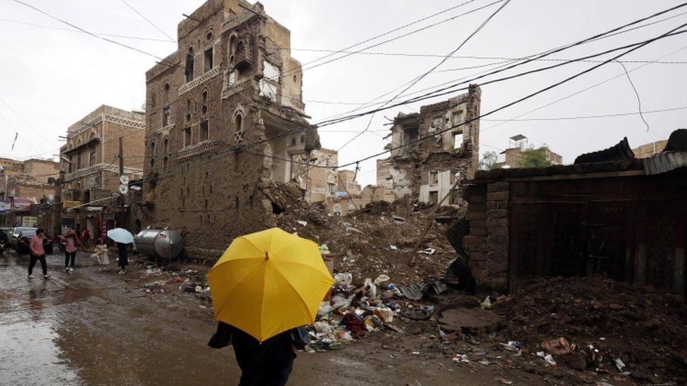 أحد اليمنيين يقف أمام مبنى مدمر.