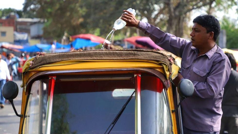 Un mototaxista echa agua en el techo de su vehículo en Nueva Delhi, India.