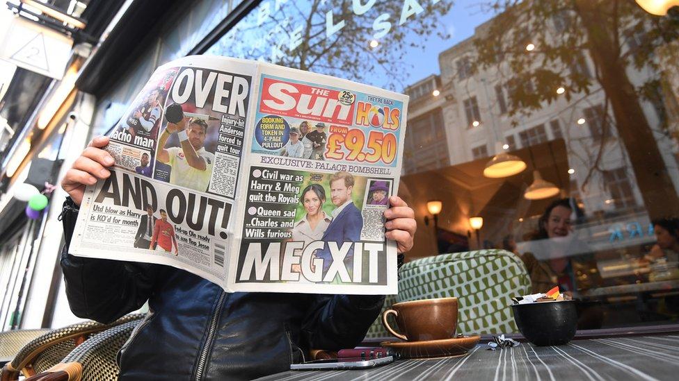 Persona leyendo el periódico The Sun en el que se habla de la decisión del príncipe Harry y su esposa Meghan de alejarse de la familia real