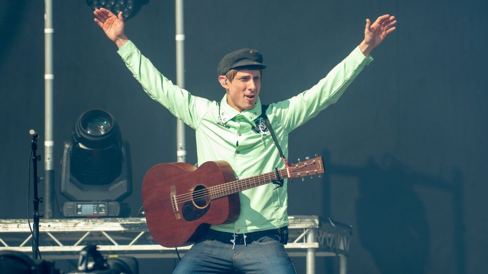 Gerry Cinnamon on stage at TRNSMT with an acoustic guitar, kneeling on the stage with his arms in the air