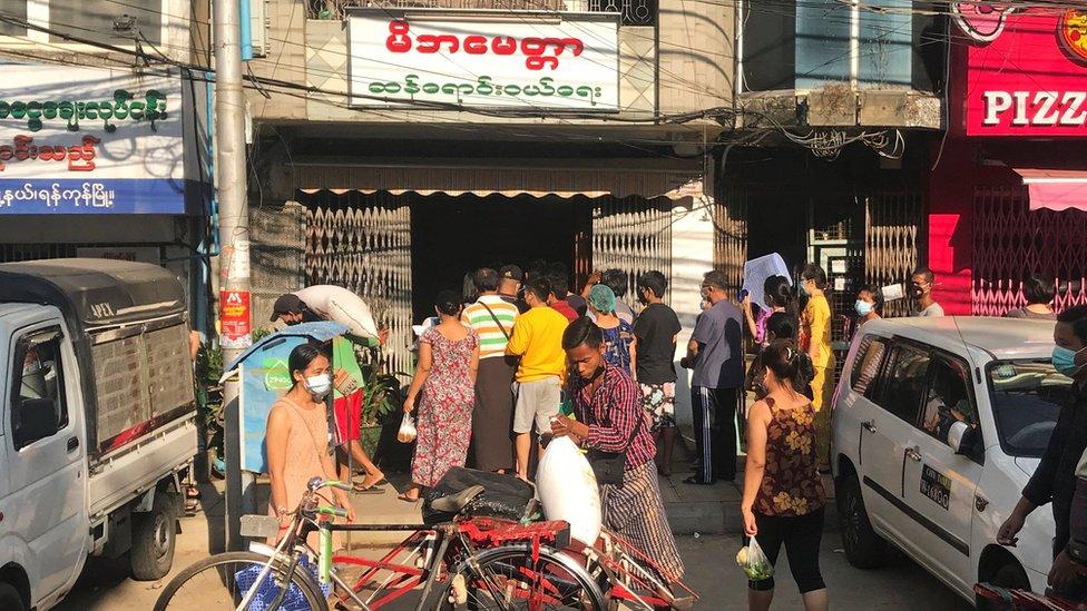 Personas haciendo fila afuera de una tienda de comestibles en Yangon.