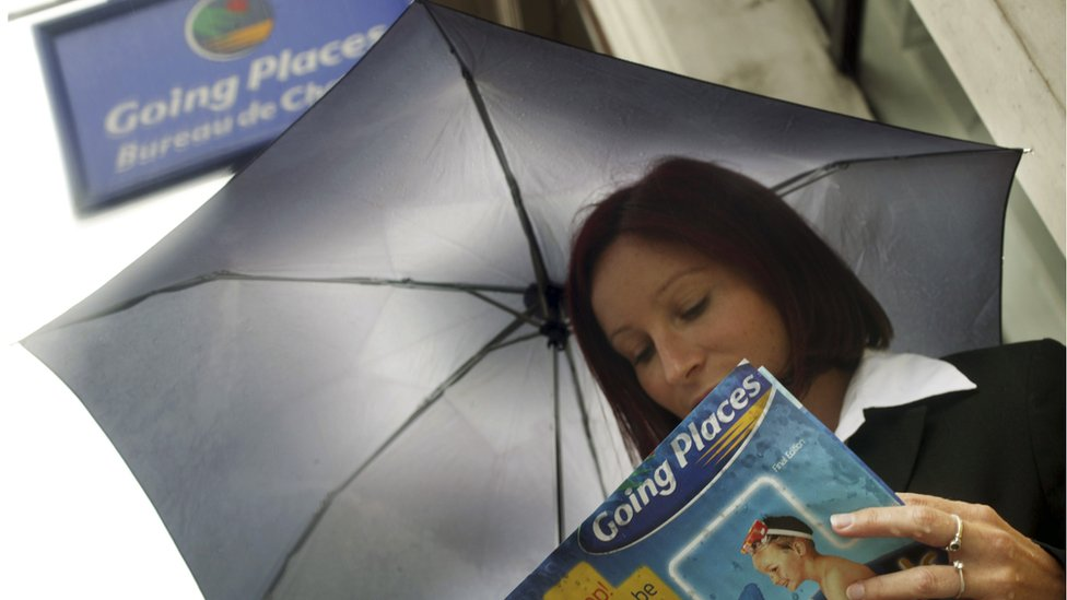 A lady contemplates getting away from the rain outside a Going Places store in London; part of the Thomas Cook Group.