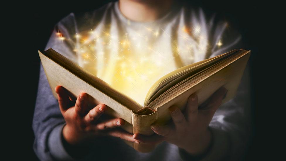 Un niños sostiene un libro del que salen luces