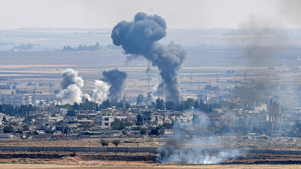 Smoke rises from the Syrian town of Ras al-Ain on 14 October 2019