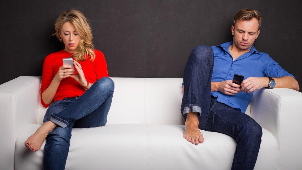 Un hombre y una mujer ensimismados con sus teléfonos inteligentes