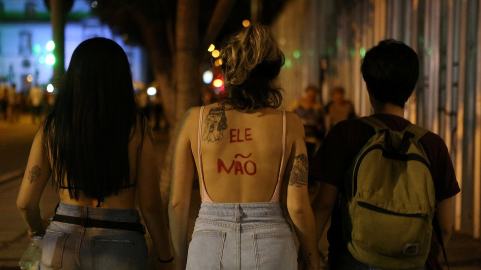 """Women, one with the words """"not him"""" painted on her back, demonstrate in Rio de Janeiro"""