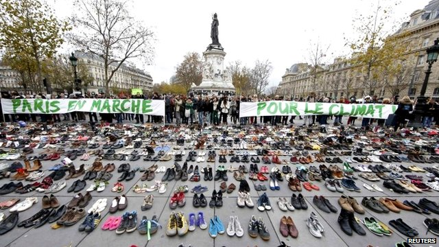 """Banners which read """"Paris marches for climate change"""" are displayed in front of pairs of shoes placed at the Place de la Republique in Paris"""