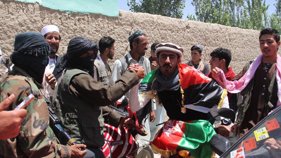 مسلح من طالبان يحمل العلم الأفغاني