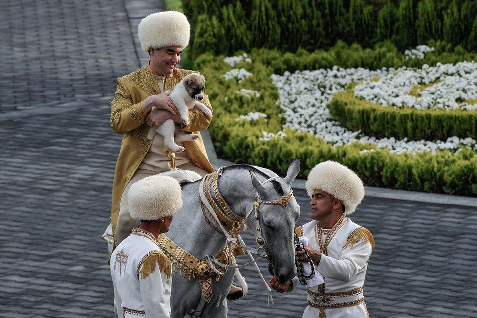 President Berdymukhamedov on a horse holding a puppy