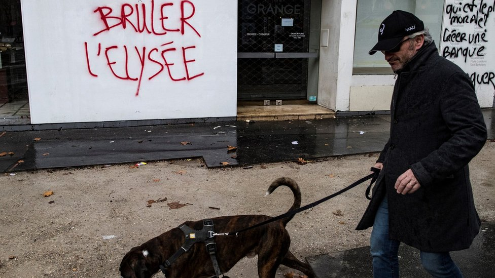 """Čovek prolazi pored grafita """"Spalite Jelisej"""""""