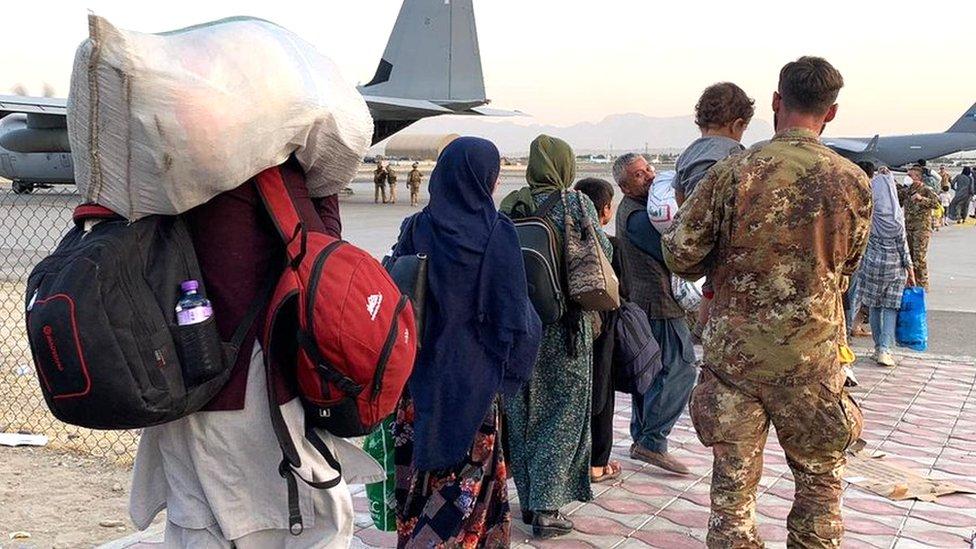 Gente caminando con sus pertenencias en el aeropuerto de Kabul.