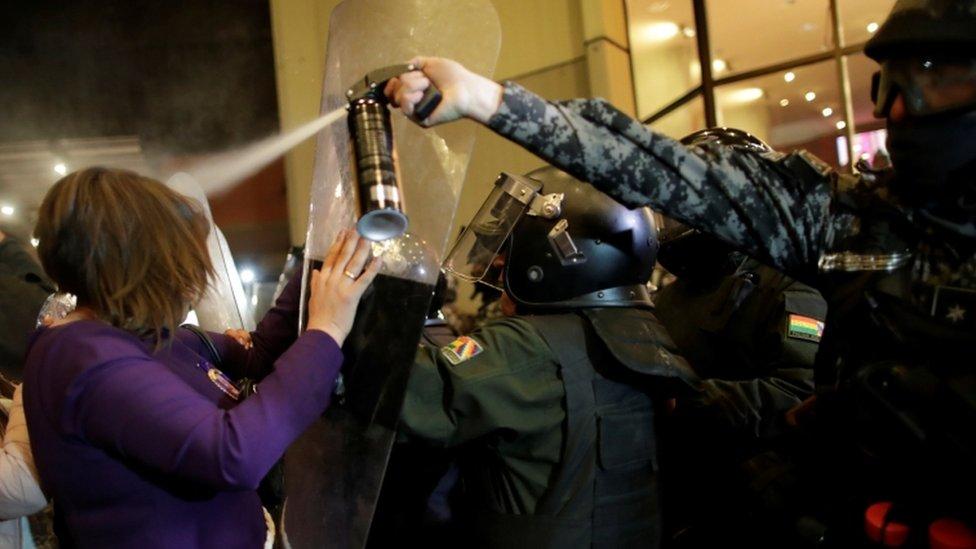 Policía gaseando a una manifestante en Bolivia.