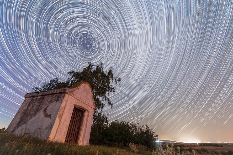 A combination of multiple long exposure photographs shows satellites and Perseid meteors crossing a starry sky over a chapel