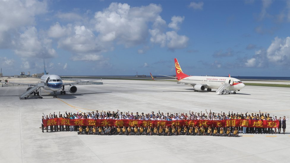 A large group of people pose for a group photo, carrying a large banner with yellow lettering on a red background, in front of two Chinese passenger jets on the airfield of Fiery Cross Reef, known as Yongshu Reef in Chinese. Taken 6 January 2016.