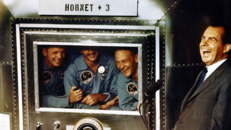 In this handout photo provided by the Richard Nixon Foundation, Apollo XI astronauts Neil Armstrong, Michael Collins and Buzz Aldrin laugh with President Richard Nixon aboard the USS Hornet, July 24, 1969.