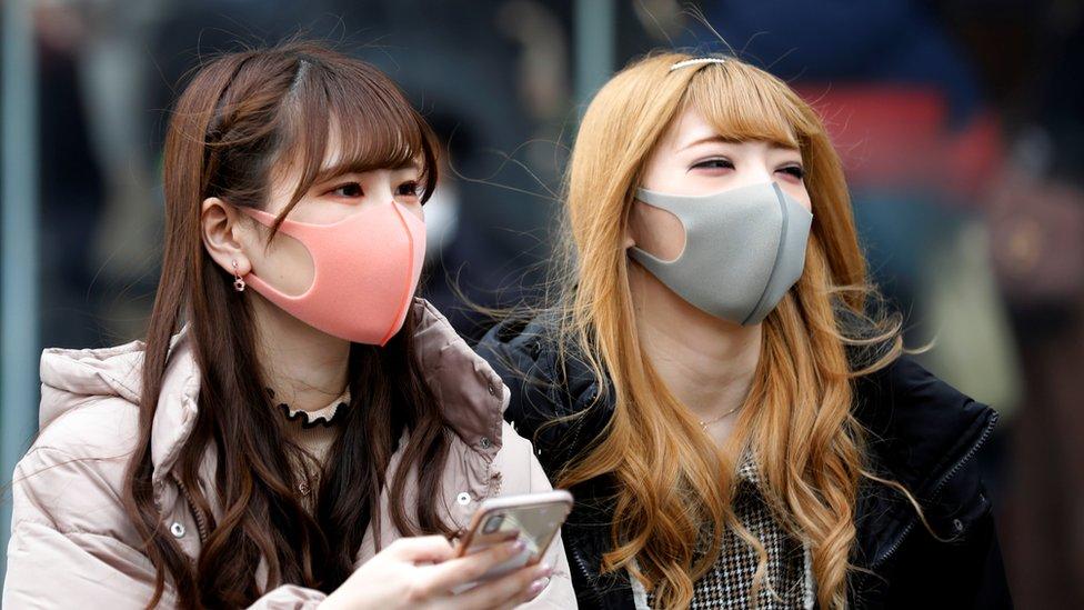 Dua perempuan menggunakan masker wajah yang berwarna merah muda dan abu-abu di jalanan Tokyo, Jepang.
