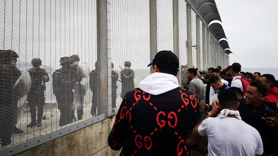 Spanish troops and Moroccan migrants at Ceuta border fence, 18 May 21