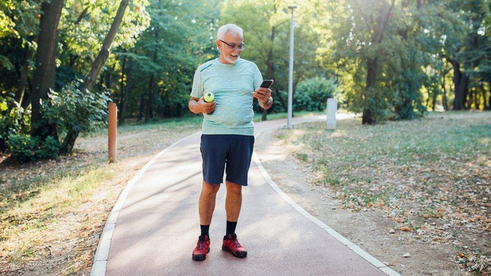 Un hombre hace ejercicio y mira el teléfono.