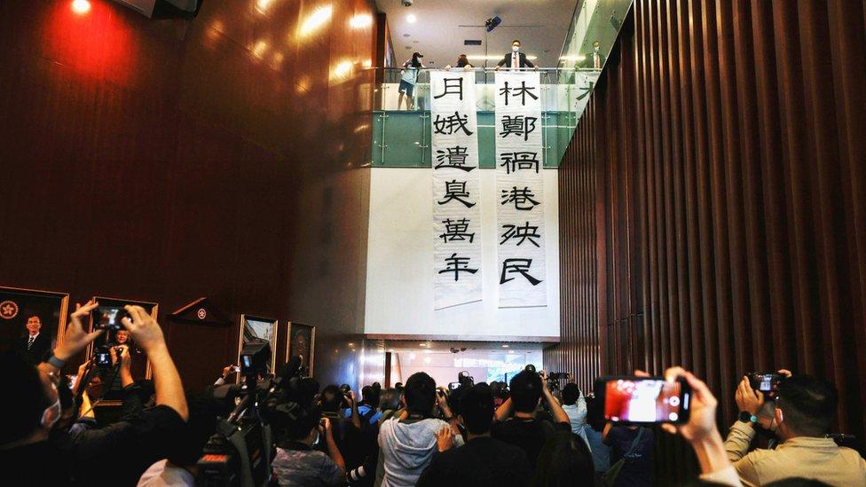 香港立法會大樓內民主黨原議員林卓廷(上層右一)在媒體面前展示大型抗議標語(12/11/2020)