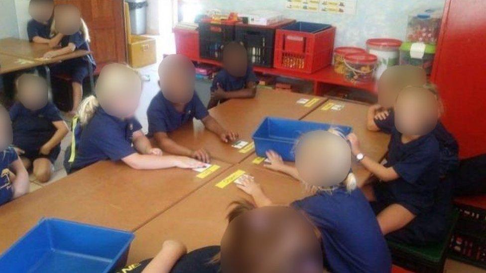 تلاميذ بيض وسمر البشرة يجلسون على طاولة واحدة
