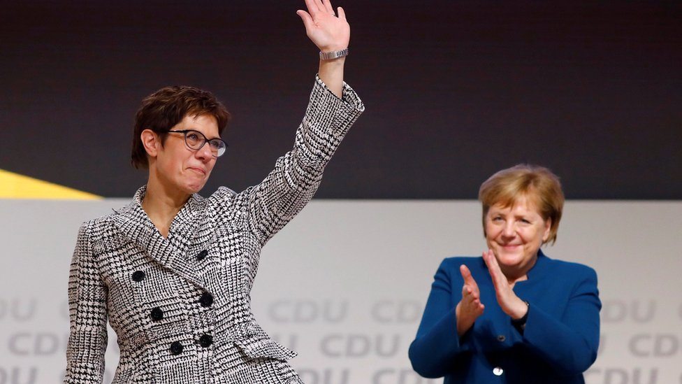 Annegret Kramp-Karrenbauer waves next to German Chancellor Angela Merkel after being elected as the party leader