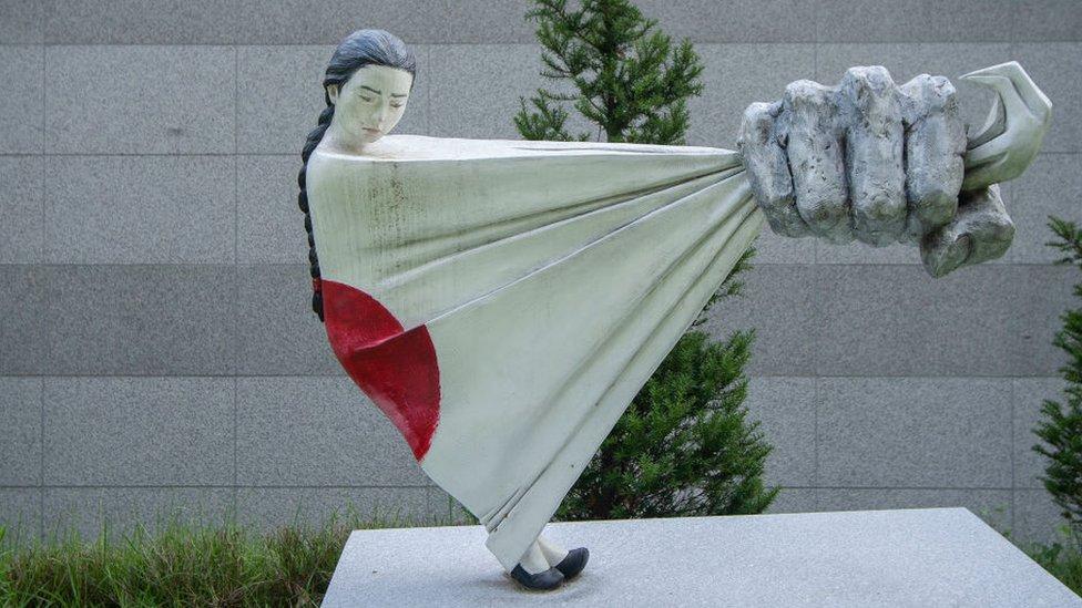 Estatua de una mujer siendo apresada por una bandera japonesa.
